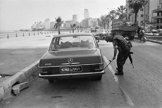 A U.S. Marine uses a mirror on a stick to check underneath a car in front of the building used as the U.S. Embassy in Beirut, Oct. 25, 1983. (Associated Press)