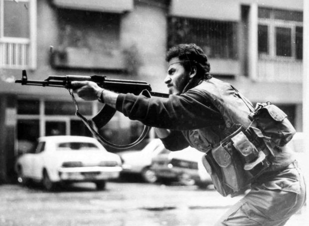 A Shiite Muslim AMAL militiaman fires his AK-47 assault rifle during skirmishes with Druse irregulars on Corniche Mazraa road, West Beirut, Lebanon, Feb. 20, 1987. (photo credit: AP)