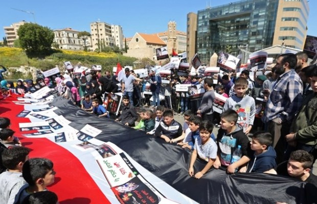 Lebanese children hold placards and a giant Yemeni flag during a demonstration organized by Hezbollah, in front the United Nations headquarters in Beirut, Lebanon, Sunday, April 5, 2015. (AP Photo/Bilal Hussein)