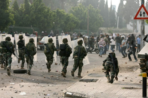 Soldiers advance towards stone-throwing Sunni Muslim supporters of outgoing Prime Minister Saad Hariri near Tariq al-Jadidah in Beirut January 25, 2011. (REUTERS/Hasan Shaaban)