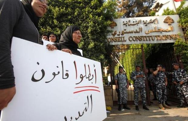 Protesters carry a sign ugring judges meeting at the Constitutional Council headquarters in Beirut to accept a challenge against Parliament's extension. (The Daily Star/Khalil Hassan)